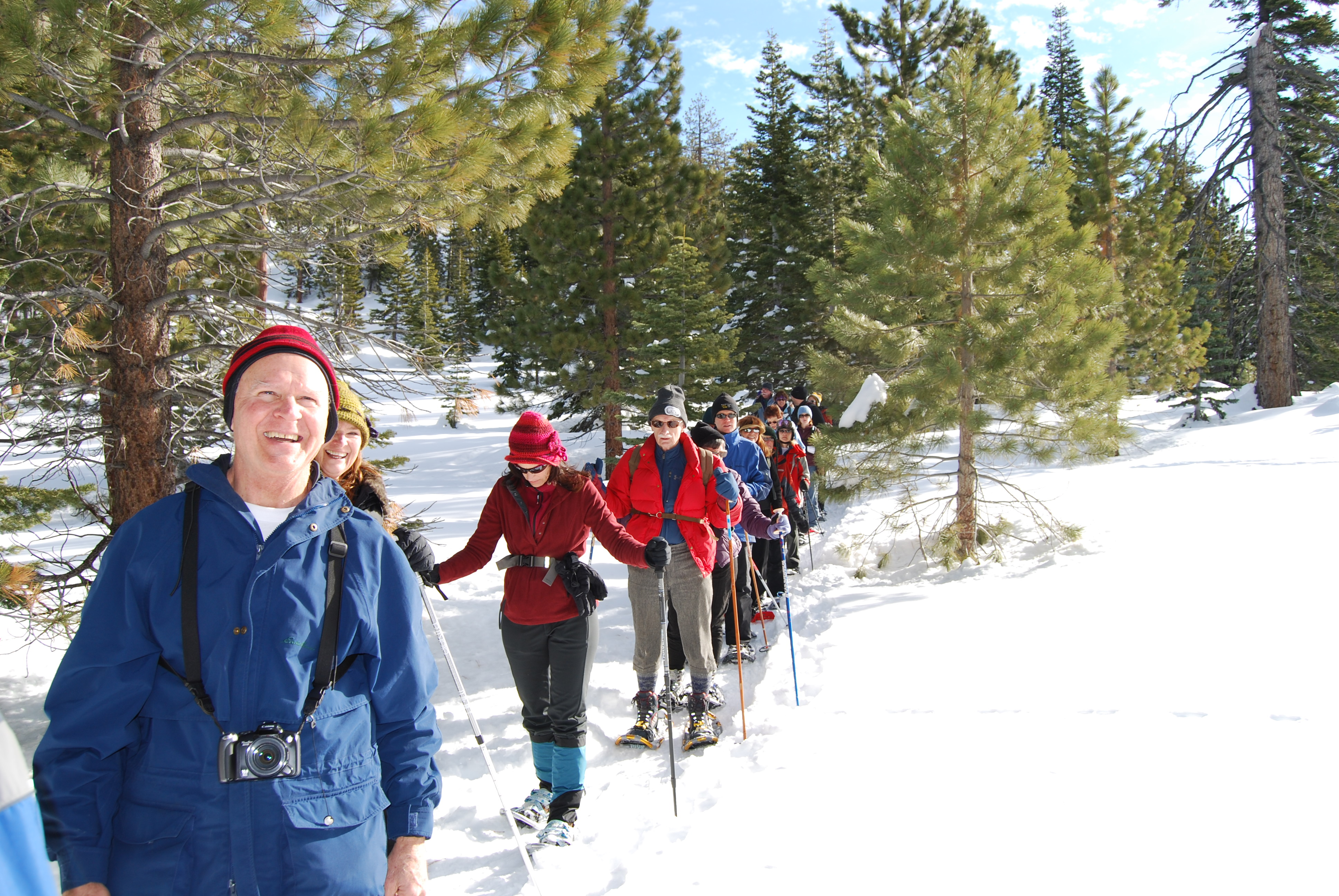 Group of people walking through snow in skis