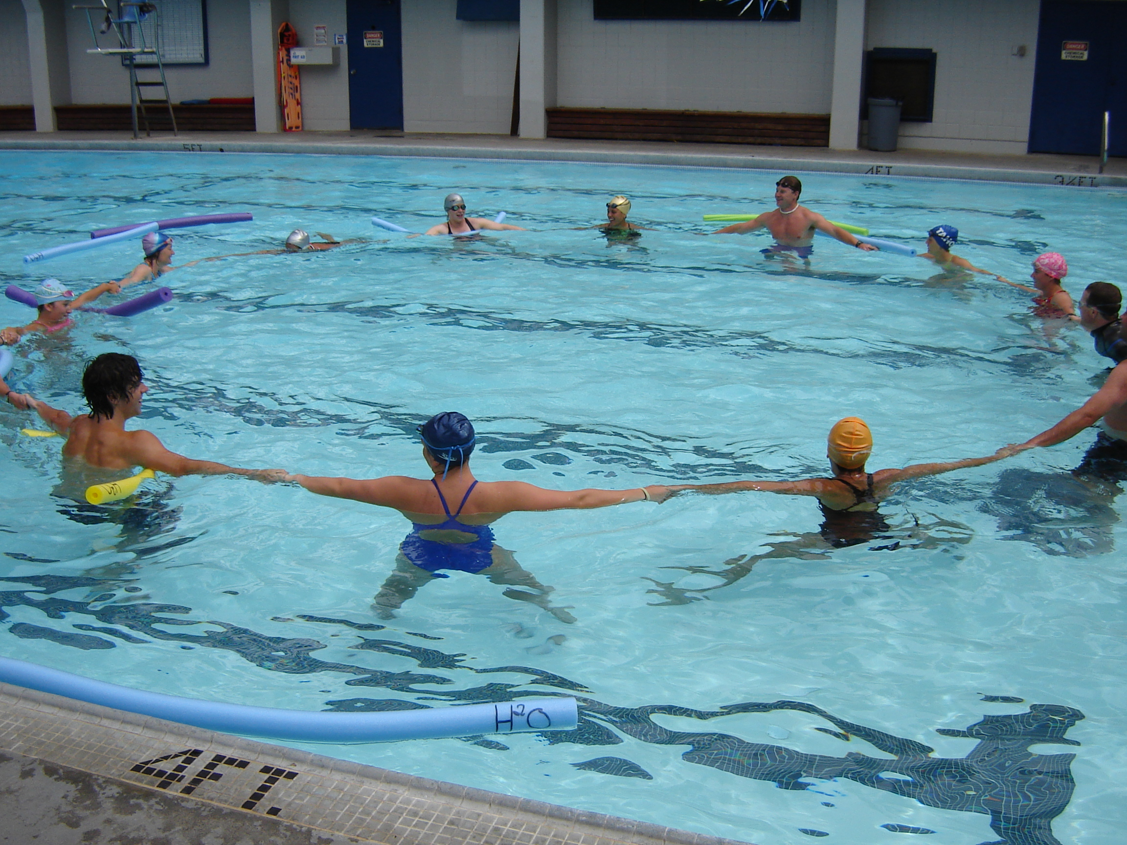 Staff forming a circle in the swimming pool