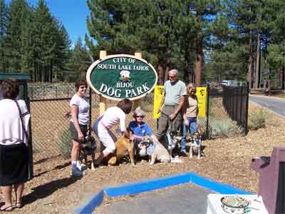 People standing by Dog Park sign