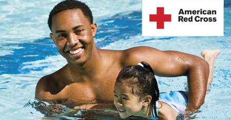 Instructor holding young girl in pool