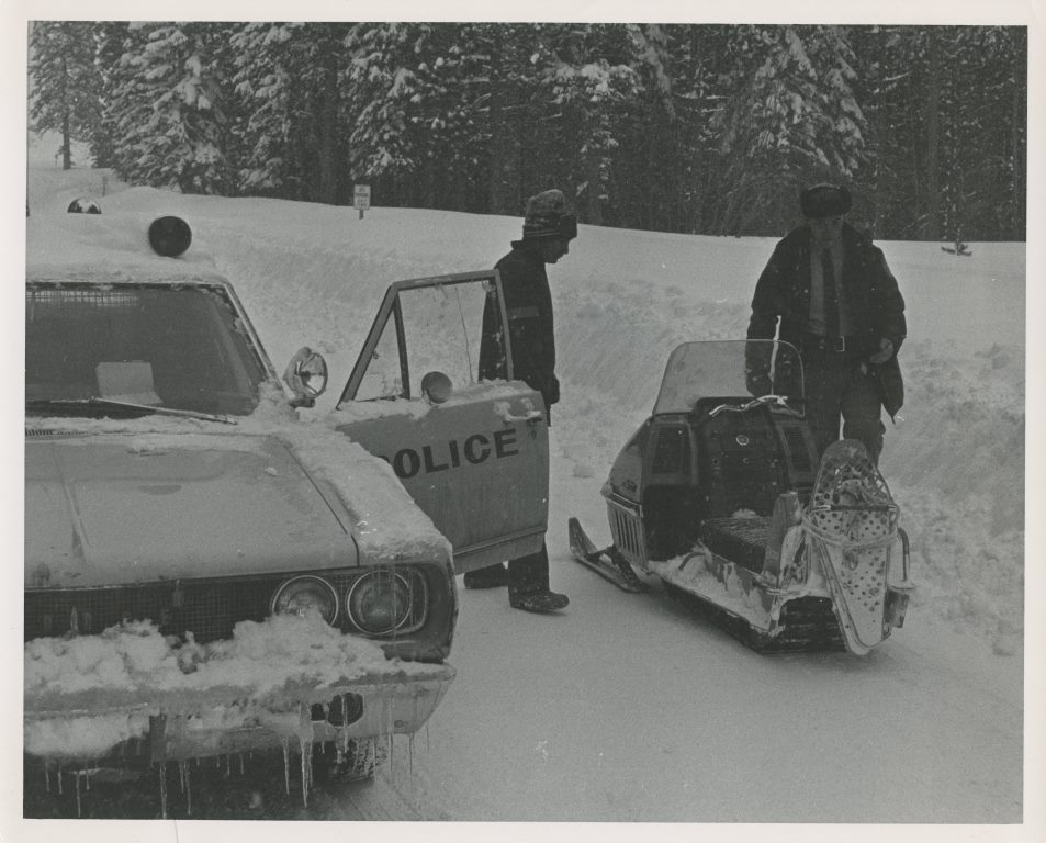 Black and white Police Car and Snow Mobile in Snow